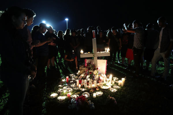 Students, friends and family pray during Thursday night's candlelight vigil.