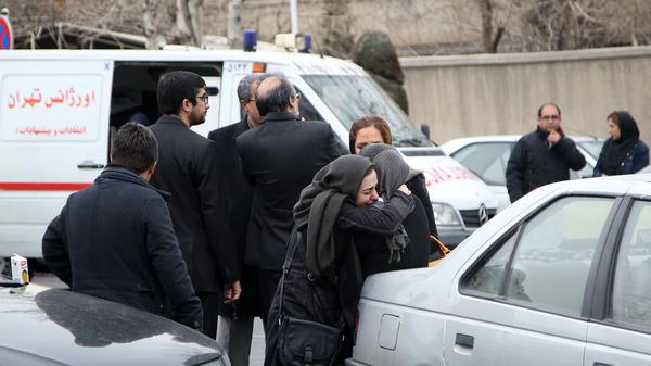 Relatives of passengers on board a plane that crashed into a mountain Sunday, mourn at Mehrabad International Airport in Tehran on Sunday. All 65 people aboard were feared dead.