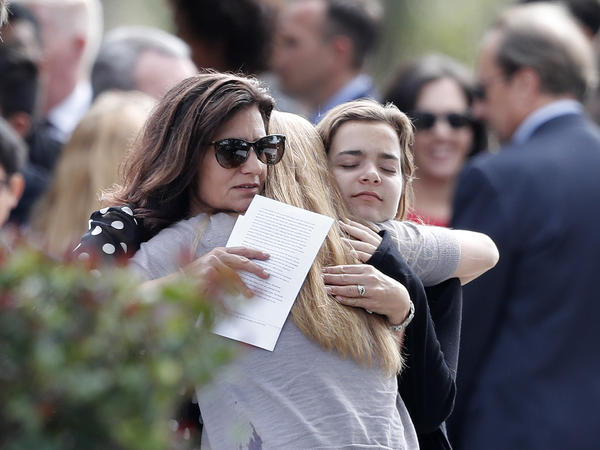 Mourners hug as they leave the funeral of Alaina Petty, in Coral Springs, Fla., on Monday. Alaina, a member of JROTC, was one of the victims of the mass shooting.