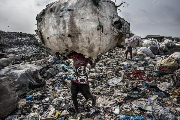 Boys carry trash in Lagos, Nigeria.