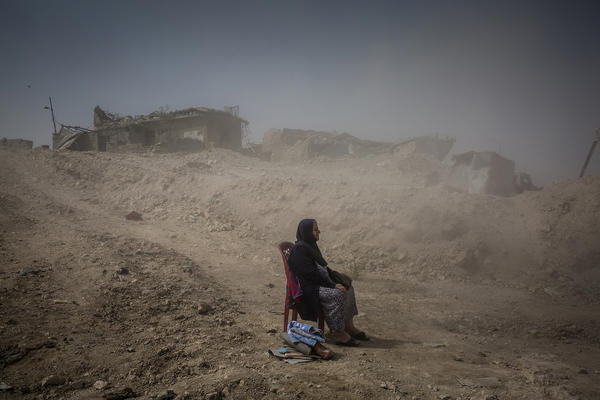 Nadhira Aziz watched as Iraqi Civil Defense workers dug out the bodies of her sister and niece from her house in the Old City, where they were killed by an airstrike in June.