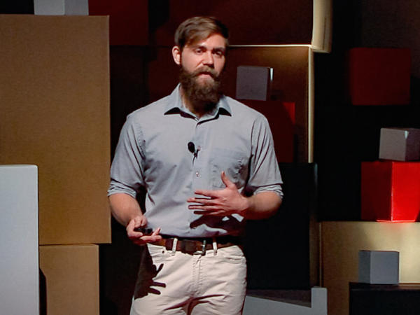 Arik Hartmann speaks on the TED stage.