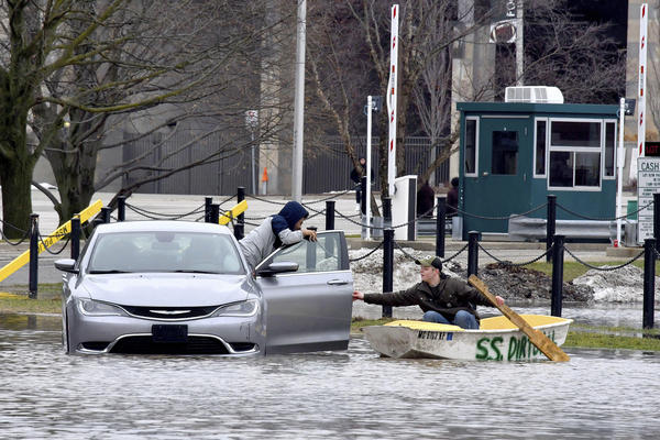 "Mathias ""Dale"" Dekker (right) piloted his boat to rescue John Parker when the Red Cedar River flooded near Michigan State University in East Lansing on Wednesday."