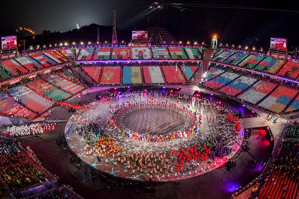 Flags of the participating nations are projected onto the stands as athletes enter the stadium. Unlike in the opening ceremony, there is no specific order for procession as all athletes come together.