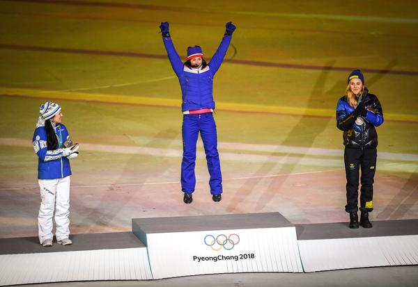 Norway's gold medalist Marit Bjoergen jumps for joy on the medal podium with Finland's silver medalist Krista Parmakoski (left) and Sweden's bronze medalist Stina Nilsson during the medal ceremony for the cross-country women's 30-kilometer mass start classic. Bjoergen has won 15 Olympic medals over her career, the most of any Winter Olympian.