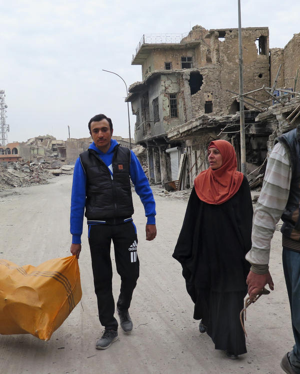 Mona Abed and her sons carry belongings they've retrieved from their Mosul home that was toppled by airstrikes.