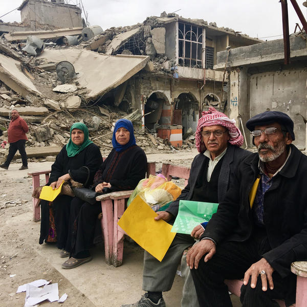 Samira Sheet (left) sits with neighborhood residents in Mosul's Old City, waiting for an aid organization they say has promised to give them money. They're holding folders with their IDs.