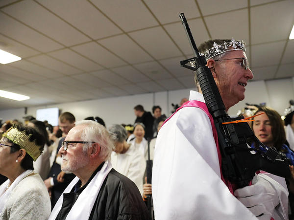 "A church official holds an AR-15 rifle during the service. One attendee told reporters that she needed her weapon to defend her family against ""sickos and evil psychopaths."""