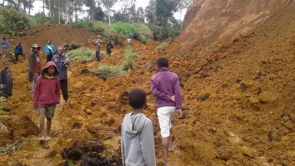 People walk at the site of a landslide near the village of Ekari in Papua New Guinea's highlands region on Tuesday, after a 7.5-magnitude earthquake struck on Monday. Communication blackouts and blocked roads are hampering rescue efforts as Papua New Guinea works to get a better grasp of the damage wrought by a massive earthquake amid fears of its economic impact.
