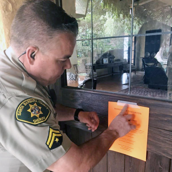 Santa Barbara County Sheriff's Deputy Mike Harris posts a notice on a home near Carpinteria, Calif., advising of the mandatory evacuation.  flash flood warnings for the area were lifted around 9:45 a.m. ET, The Associated Press reports.