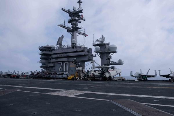 Fighter jets as well as early warning aircraft and helicopters are parked near the control tower of the USS Carl Vinson in the South China Sea.