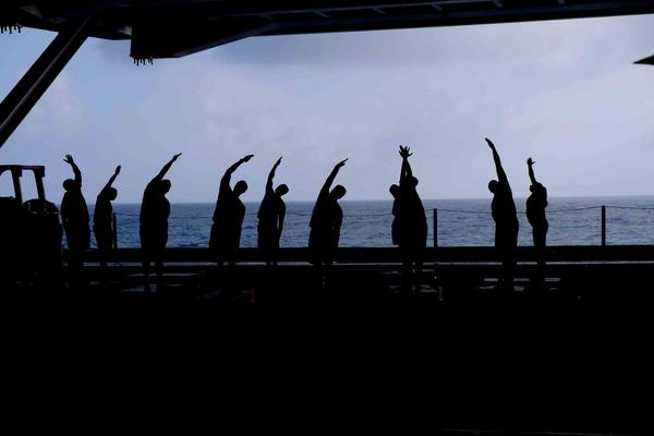 Crew members exercise in the hangar bay below the flight deck of the USS Carl Vinson in the South China Sea.