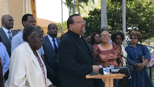 Rev. Anthony Burrell, at lectern, with other local clergy gathered to show support for Sheriff Scott Israel.