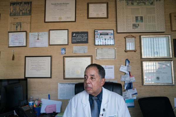 Dr. Chapman in his office at the end of the day on Friday. He waits for the last patient to come in, not wanting them to have to spend the weekend without medication. The walls are covered with awards, certificates, newspaper clippings and family photos.