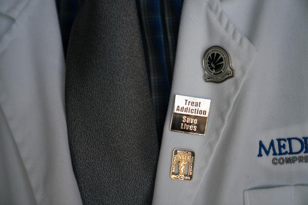 Chapman wears pins that signify his commitment to treating patients fighting addiction.