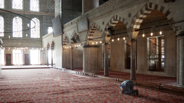 An old man prays inside Sultan Ahmed mosque in Istanbul, Turkey.