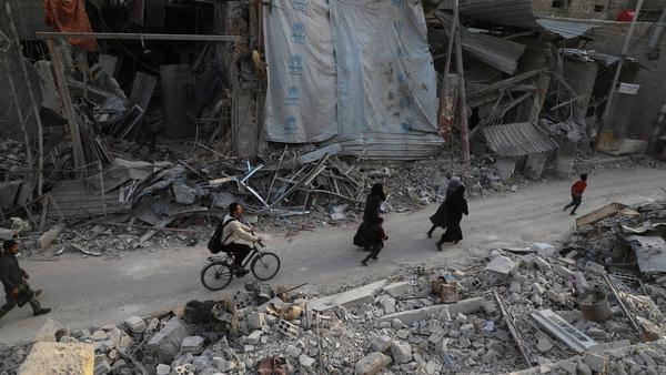 Syrian civilians run after an aid covoy, not pictured as it entered the rebel enclave of Eastern Ghouta on Monday. The same day the Syrian regime pounded the region with fresh bombardment, killing dozens as it seized more ground.