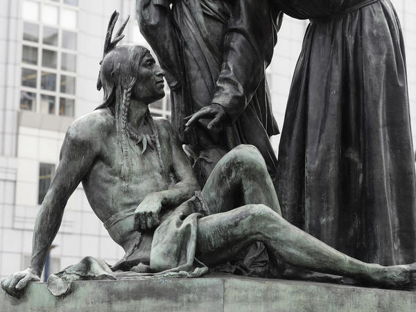 A statue of a Native American sitting below a vaquero and a missionary in San Francisco.
