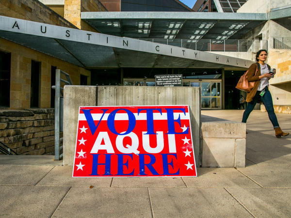 A pedestrian walks past Austin City Hall, an early voting center, on Tuesday in Austin, Texas.