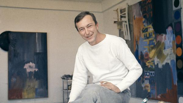 Jasper Johns, pictured in his New York City studio in 1964, was known for transforming common objects like flags, numerals and archery targets into unsettling paintings.