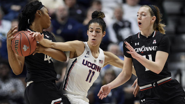 At the American Athletic Conference tournament semifinals earlier this month in Uncasville, Conn., Cincinnati's Andeija Puckett, left, looks to pass to Sam Rodgers, right, under pressure from Connecticut's Kia Nurse. Connecticut is the first overall seed in the NCAA women's basketball tournament that begins on Saturday.