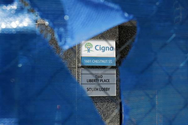 The Cigna logo is seen behind a construction fence, Friday, March 9, 2018, in Philadelphia. The insurer Cigna will acquire the nation's biggest pharmacy benefit manager, Express Scripts, the latest in a string of proposed tie-ups as health care's bill payers attempt to get a grip on rising costs. Cigna CEO David Cordani said Thursday, March 8, that the combined company will make health care more simple for customers. (Matt Slocum/AP)