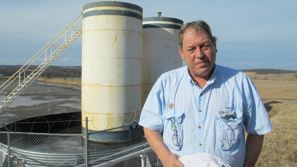 Jim Barrett stands next to a well pad on his farm in Bradford County, Pa. He accuses Chesapeake Energy of cheating him out of royalty money.