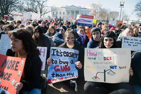 Thousands of local students sit for 17 minutes in honor of the 17 students killed last month in a high school shooting in Florida, during a nationwide student walkout for gun control in front the White House in Washington, D.C.