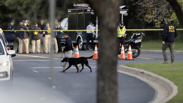 Officials work Monday near the site of the latest explosion in Austin. Police warned nearby residents to remain indoors overnight as investigators looked for possible links to other deadly package bombings elsewhere in the city this month.