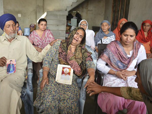 Hardeep Sing (left) and Sushwinder Kaur (center) mourn holding portraits of their son Manjinder Singh, one of the 39 Indian workers whose bodies were found buried northwest of Mosul.