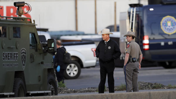 Officials investigate the scene in Round Rock, Texas, where a suspect in a series of bombing attacks in Austin blew himself up early Wednesday as authorities closed in.