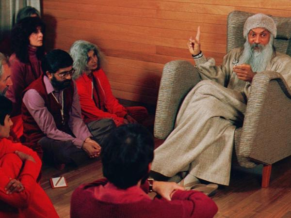 Bhagwan Shree Rajneesh, right, speaks with his disciples in this undated photo in Rajneeshpuram, Ore.