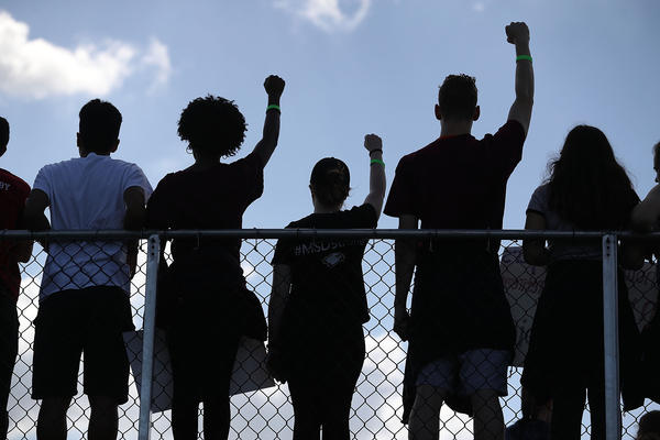 Marjory Stoneman Douglas High School students hold their fists up in the air as they participate in the March For Our Lives event at Pine Trails Park before walking to the high school in Parkland, Florida.
