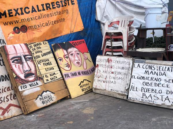 Handmade signs decorate the corner where Mexicali Resiste has camped in protest of privatization of the city's water.