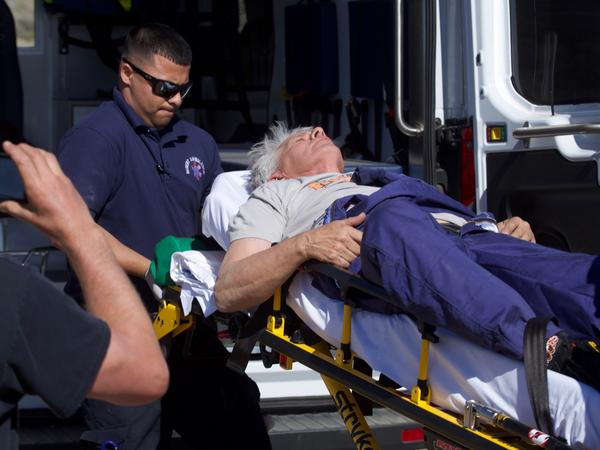 Medical professionals pull Hughes' stretcher aboard an ambulance after his rough landing left him in less than ideal condition.
