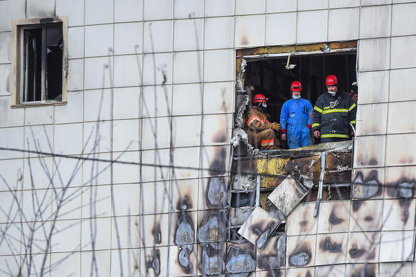 Russian emergency service staff work at the site of a fire at a multi-story shopping center in Kemerovo.