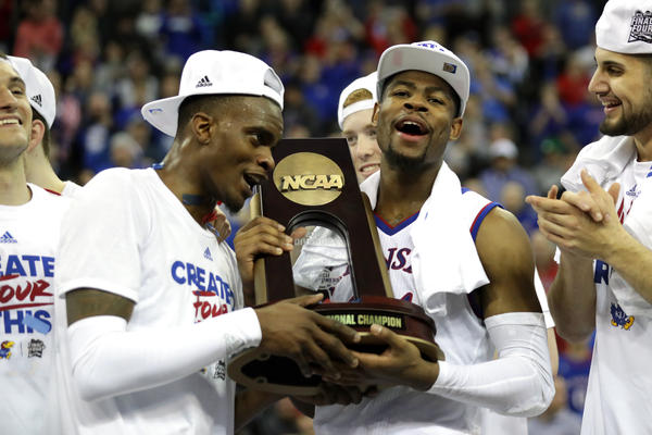 Lagerald Vick (left) and Malik Newman (right) of Kansas celebrate with the regional championship trophy after defeating Duke in the Midwest Region.