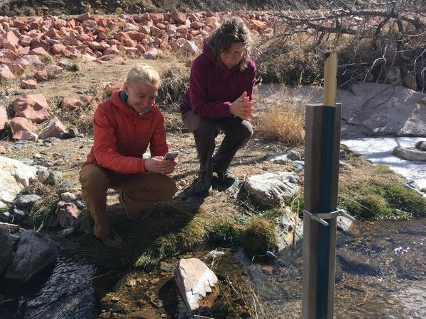 Kira Puntenney-Desmond, left, and Stephanie Kampf inspect the water level in a stream in Poudre Canyon, Colo., and record it on a smartphone app. Wildfires and flooding have reorganized area streams.