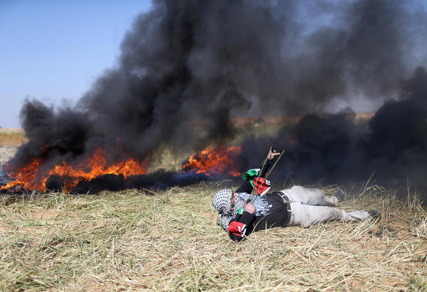 A Palestinian hurls stones at Israeli troops during clashes at the Gaza-Israel border at a protest demanding the right to return to their homeland, in the southern Gaza Strip.