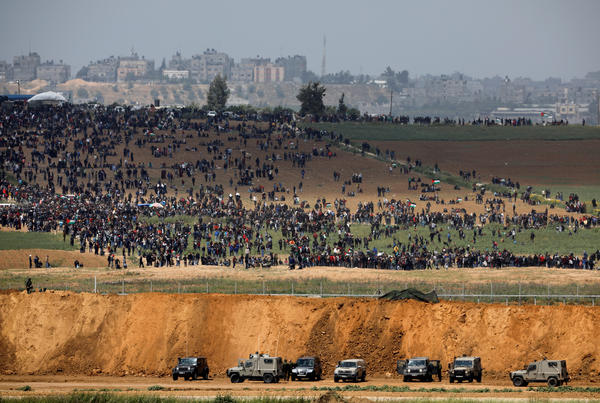Israeli military vehicles are seen next to the border on the Israeli side of the Israel-Gaza border, as Palestinians demonstrate on the Gaza side of the border on Friday.