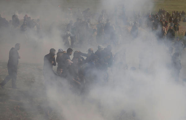 Palestinians run from tear gas fired by Israeli troops during clashes, during a tent city protest along the Israel border with Gaza, demanding the right to return to their homeland, east of Gaza City Friday.