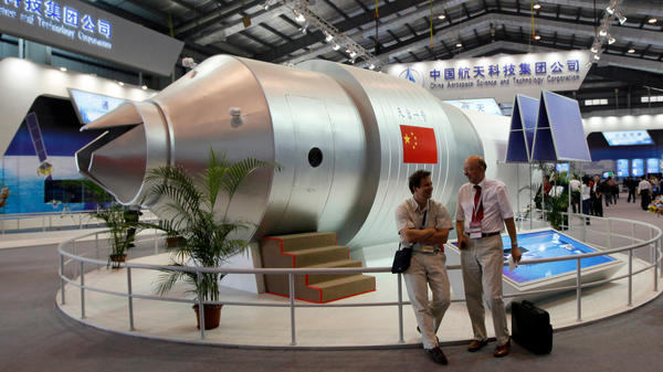 Visitors sit beside a model of China's Tiangong-1 space station in 2010, at the 8th China International Aviation and Aerospace Exhibition in Zhuhai in southern China's Guangdong Province. As forecast, China's defunct Tiangong 1 space station re-entered Earth's atmosphere Sunday.