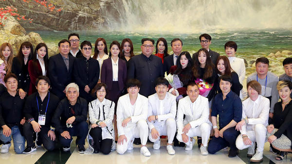 A picture provided by North Korea's official Korean Central News Agency shows North Korean leader Kim Jong Un (back, center) and his wife Ri Sol-Ju (second row, sixth from left) posing with South Korean musicians after their performance in the East Pyongyang Grand Theater in Pyongyang.