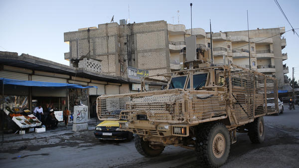 "A vehicle of U.S. troops passes on a street in Manbij, Syria on Saturday. President Trump's unscripted public declaration this week about pulling out of Syria ""very soon"" while at odds with his own policy are unnerving for the Kurds in this context."