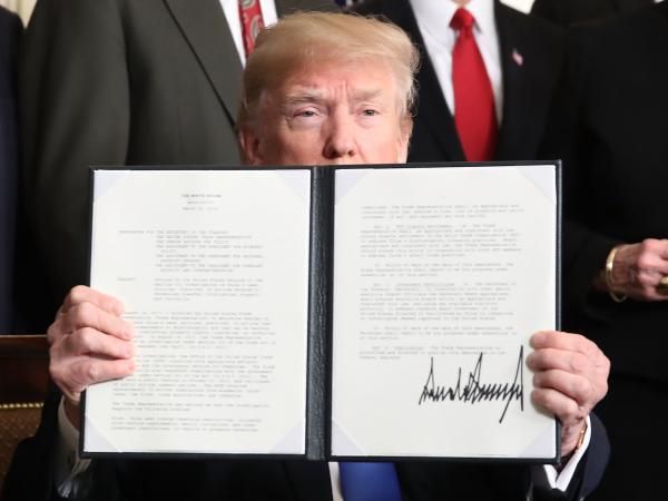 President Trump holds up a signed presidential memorandum aimed at what he calls Chinese economic aggression in the Roosevelt Room at the White House on March 22, 2018.