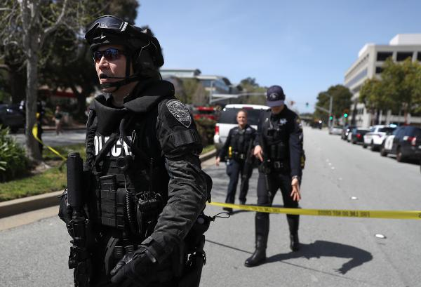 Law enforcement stands watch outside of the YouTube headquarters on Tuesday in San Bruno, Calif. Police are investigating an active shooter incident at YouTube headquarters that has left at least one person dead and several wounded.