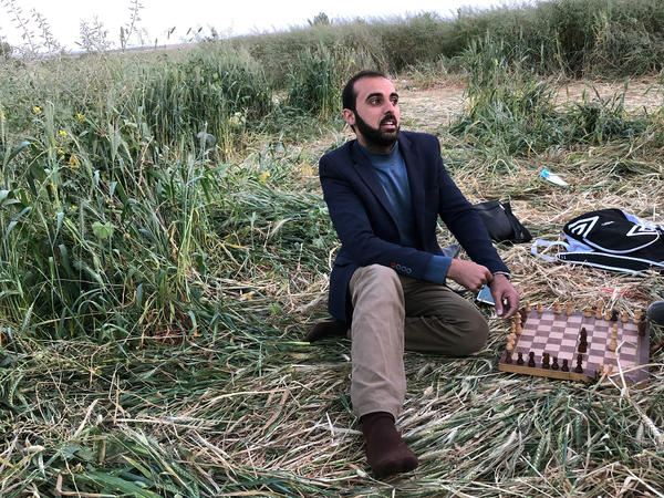 Jaber Abu al-Amrein,<strong> </strong>24, sits in a barley field near the Gaza border and plays chess with a friend. Palestinians are gearing up for another Friday of large and potentially bloody demonstrations.