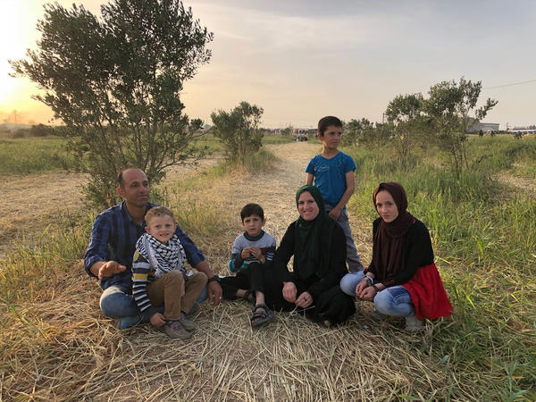 A Palestinian family sits in a field close to the border.