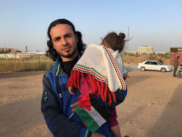 Sameh Sarsak, 33, holds his daughter. He is a trained nurse and is unemployed.