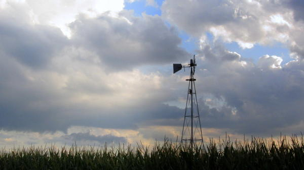 A windmill outside Swanton, Neb., sets an idyllic scene. The satirical podcast <em>A Very Fatal Murder </em>is set in the fictional small town of Bluff Springs, Neb.